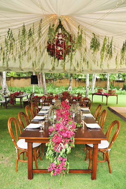 flower installation of hot pink bougainvilleas above dinner tables with hanging greeneries and flowers