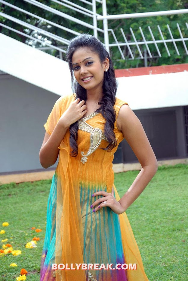 Chandini doin various elegant poses in a garden  - chandini in sleeveless yellow suit