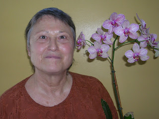 Light-skinned Latina woman with round face and rosy cheeks smiling next to a vase of pink flowers. She has very short dark hair gone mostly gray and is wearing an embroidered orange-brown shirt.