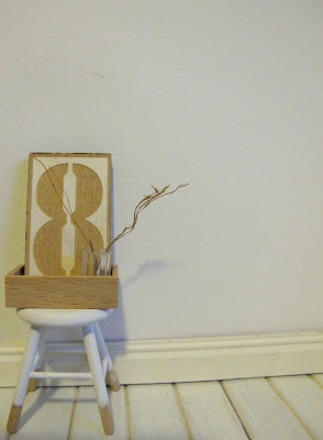 Modern dolls' house miniature stool with raw wood legs and white-dipped top part., displaying a letter eight in a wooden box, along with a glass with twigs in it.
