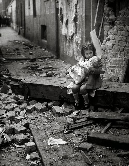 Маленькая девочка с куклой, сидящая в руинах ее разбомбленного дома, Лондон, 1940 г.