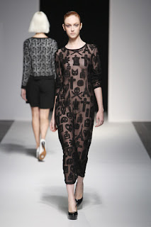 A model wearing a sheer black dress decorated with crosses on the Devastee catwalk