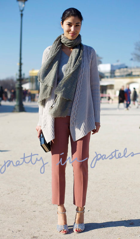 Woman wearing coral ankle length pants, a chunky cream sweater with a pale green woven scarf. She's holding a black clutch purse with silver clasp and strapy, peep toe metallic heels