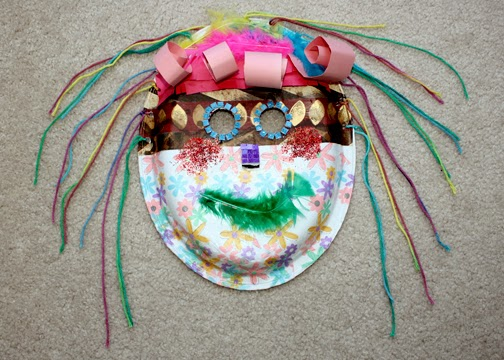 """Tessa used a heavy duty oval paper plate, wrapping and tissue paper, yarn, feathers and a variety of other craft supplies to create an """"African"""" mask during Atelier art time."""