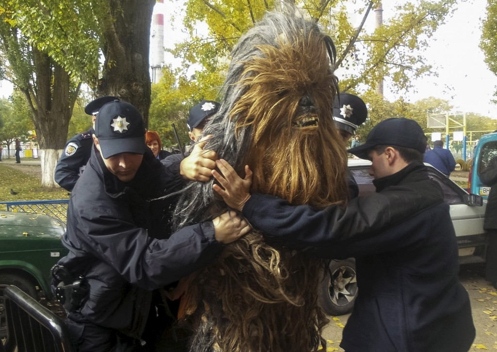 70 Of The Most Touching Photos Taken In 2015 - Ukrainian policemen detain a man dressed as Chewbacca for illegal election-day campaigning in Odessa during mayoral elections.