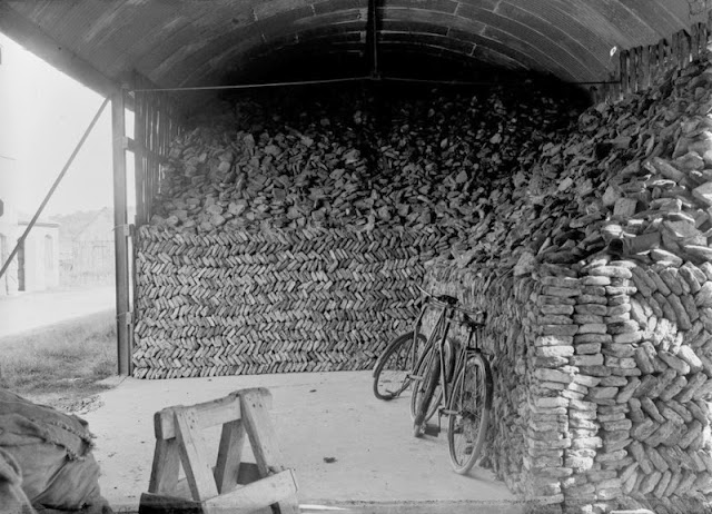 Black Moss, 2.4 km. north of Dinnet Station. Aberdeenshire. Inside the large kieselguhr (diatomite) storage sheds. The photograph shows the method of building and piling the dried kieselguhr blocks within the sheds. The blocks are arranged in a herringbone fashion. Two bicycles are propped against the blocks.