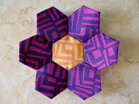 http://www.patchworkposse.com/how-to-sew-a-hexagon-flower/