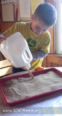 Pouring play sand into a tray for sensory letter writing: STEMmom.org