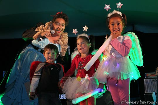 The MC with fancy dress kids L-R: Lorenzo Apuwai, 3, Napier, Indy Arbuckle, 3, Dunedin, Aaliyah Arbuckle, 5, Dunedin, at Fiesta of Lights, Hawke's Bay Showgrounds, Hastings, on New Year's Eve. photograph
