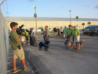 Shot of the film crew shooting the puppy raisers and pups watching the helicopter. Photo by Carolyn Hersh.