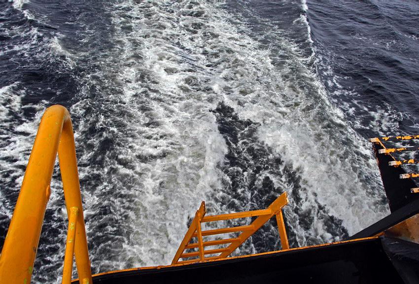 Foto à parte de trás de um barco, captando apenas a escada deste e o rasto da navegação na água