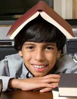 A smiling boy with an open book on his head