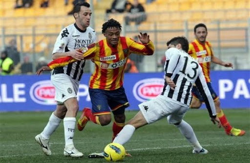 Lecce player Juan Cuadrado runs past Siena defender Luca Rossettini before scoring a goal