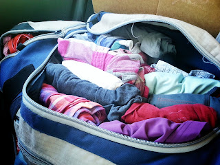 Clothes packed in a duffel bag