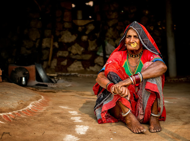 An old lady sits on the ground of her small hut dressed in a red dress in Rajasthan, India