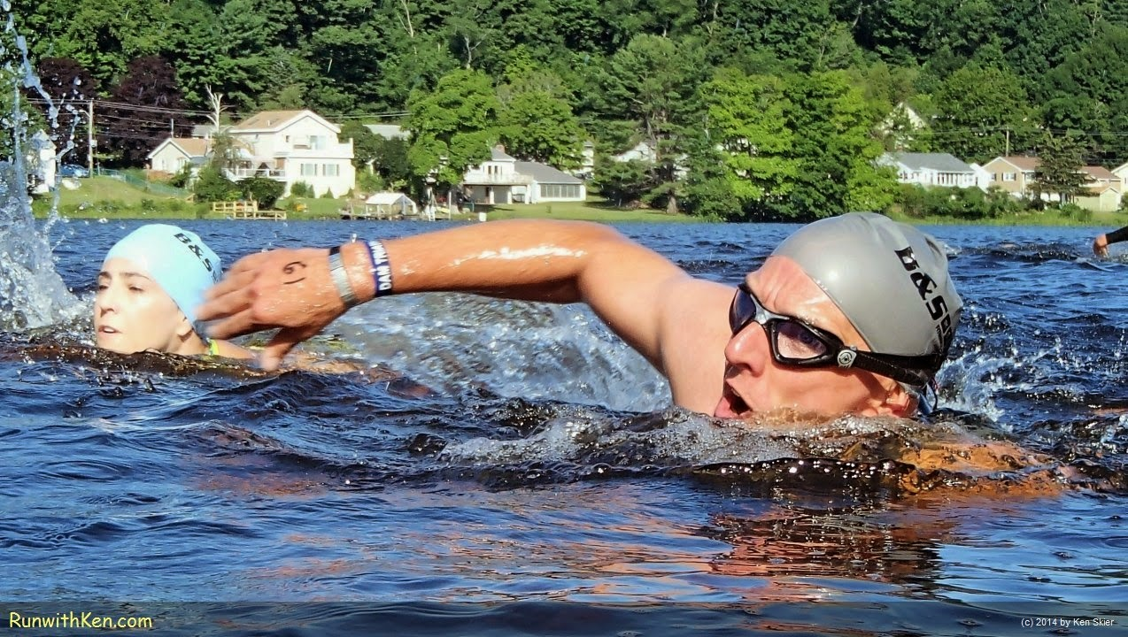 Up-close action photo of a triathlete, open water swimming at the Dam Triathlon in Amesbury, MA. Sports Photography from Inside the Pack by Ken Skier, the Swimming Photographer. (RunwithKen.com)