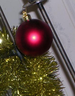 Guldglitter och röd julkula på golvljusstake. foto: Reb Dutius