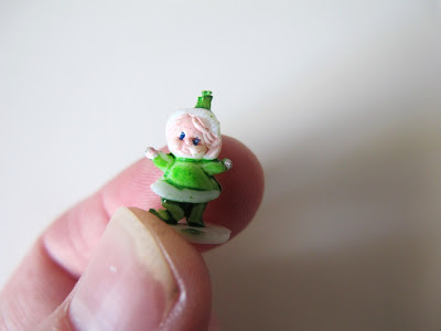 Tiny dolls' house miniature gnome ornament, being held between a finger and a thumb.
