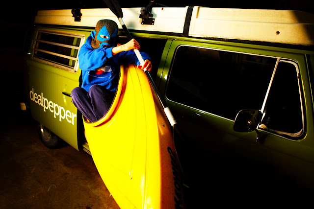 A kayaker wearing a ski mask paddling out of a gypsy green Volkswagen van.