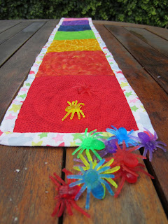 Coloured toy spiders on colour sorting quilted mat
