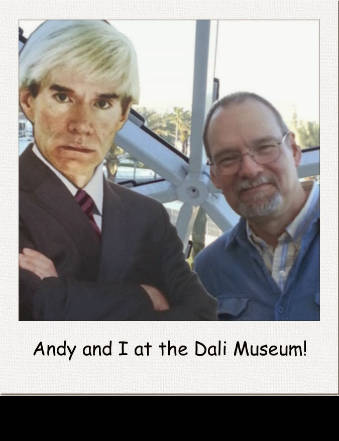 The author poses with a cardboard cutout of Andy Warhol