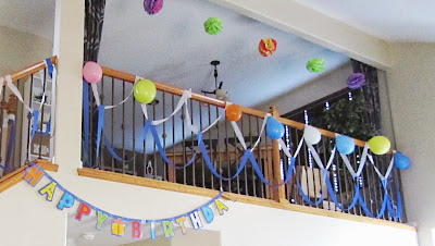 Birthday party tissue paper pom-poms, balloons, and streamers