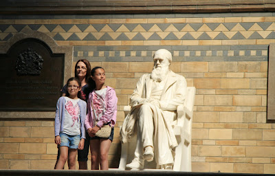 A Group Poses Next to Darwin, Girl Sneaks a Peak at Darwin