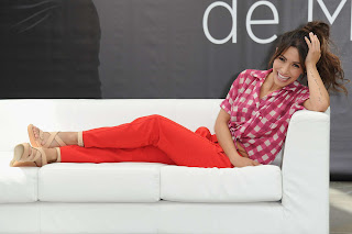 Sarah Shahi comfy on white sofa and smiling during a photo shoot in Monaco
