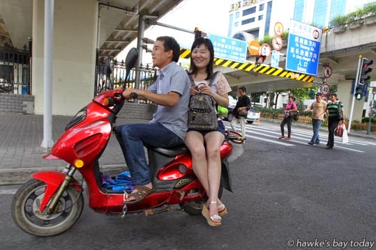 Sitting side-saddle on a scooter photograph