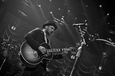 Justin Timberlake holding an acoustic guitar, black and white photo