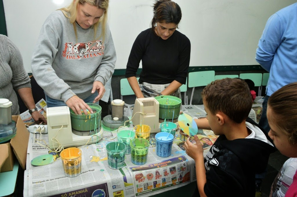 Educadores e alunos da Escola Antonio Santiago colorem CDs para decorar o ambiente escolar