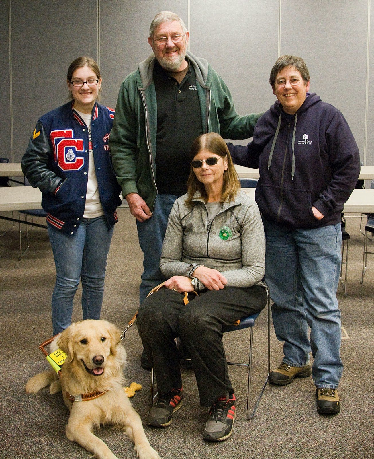 This is a group shot of the teenager (far left, standing), the man (middle, standing), the short woman (far right, standing), the woman with the sunglasses (sitting in a chair in front of the other three) and the golden retriever lying on the floor to the right of the sitting woman. Everyone, even the dog is smiling.