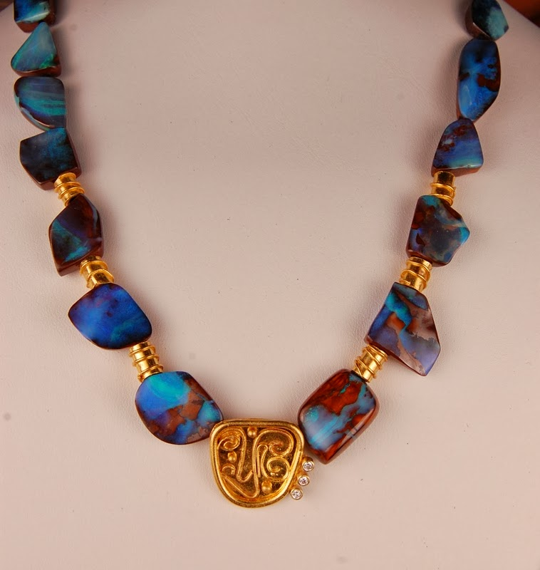 necklace composed of blue opal beads with gold spacers and a gold center piece.