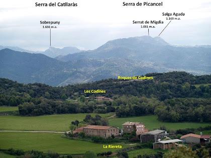 Les masies de La Riereta i Codines amb les Serres del Catllaràs i Picancel al seu darrere, des del dipòsit de l'Hostal del Gran Nom