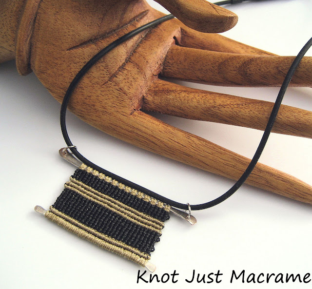 Necklace with macrame on wire pendant hung on black cord.