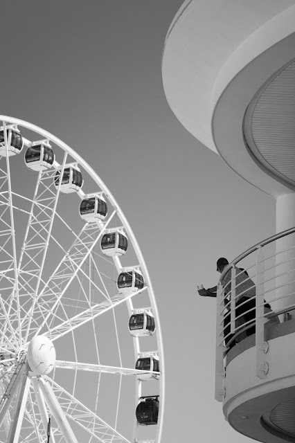 Street photograph of man leaning over balcony looking at the wheel of excellence Cape Town