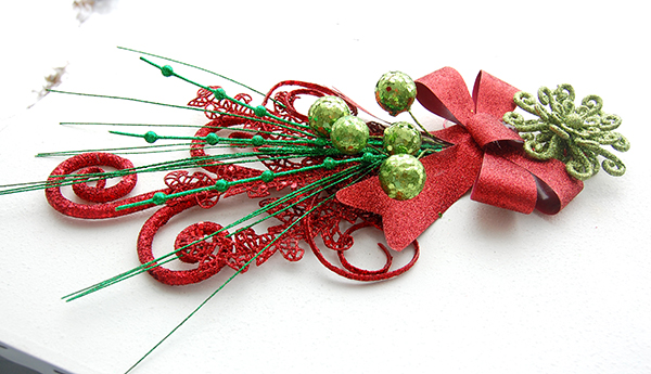 red swirl pick, red and green pick, red ribbon, green swirl ornament upclose