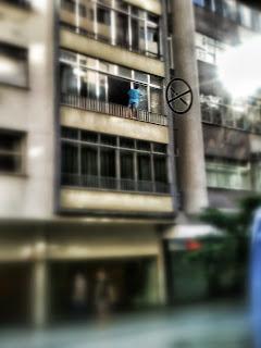 Homem se pendura ao lado de fora de uma janela para limpá-la.