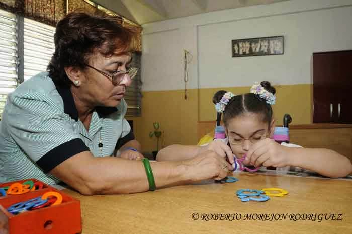 Una docente controla a una pionera que realiza ejercicios de habilidades en la escuela especial Solidaridad con Panamá, en La Habana, Cuba, el 9 de septiembre de 2014.