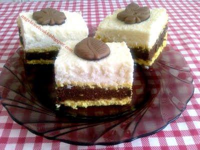 Kókuszos rumos szelet, vanília pudingos tésztával, baracklekváros kekszes kakaós töltelékkel és csokoládé levélkével díszítve.
