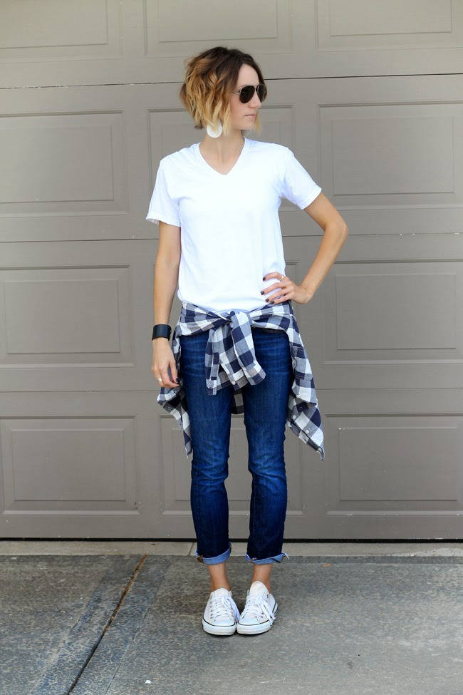 White v-neck, dark denim and a plaid shirt tied around the waist
