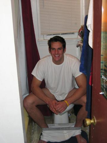 The man sitting on the toilet in a restroom and thinking