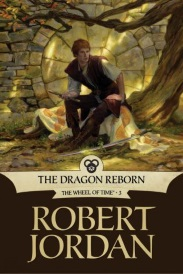 Cover of The Dragon Reborn, featuring a young, redheaded white man sitting on a large tree root near an old stone wall.