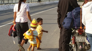 A small Vietnamese child looks at tourists on motorcycles near the border of Laos in Vietnam.