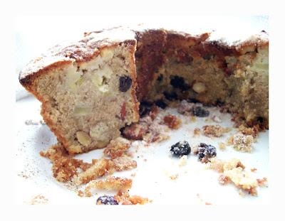 Sobre uma superfície branca, resquícios da massa do bolo, uvas-passas açucaradas e a metade de um bolo partida ocupando a parte superior da imagem. À esquerda, na parte seccionada, são vistos  pequenos pedaços de maça, uvas-passas e amêndoas incorporadas na massa.