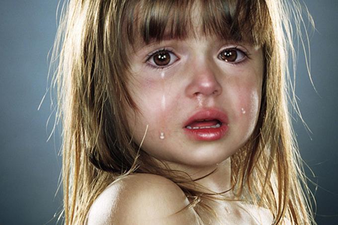 بنت صغيرة بشعر طويل تبكي بشدة والدموع تسيل على خدود وجهها