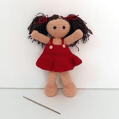 Amigurumi de muñeca con dos coletas y aguja de ganchillo