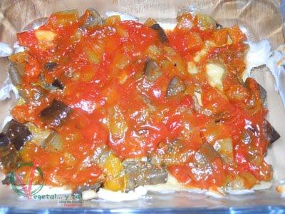 Sobre las verduras una copa de tomate frito.