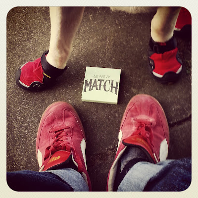 "Shot looking down at JR's red Puma shoes with Griff's red Ruffwear booties and it between them on the pos-it it reads ""We are a match."""