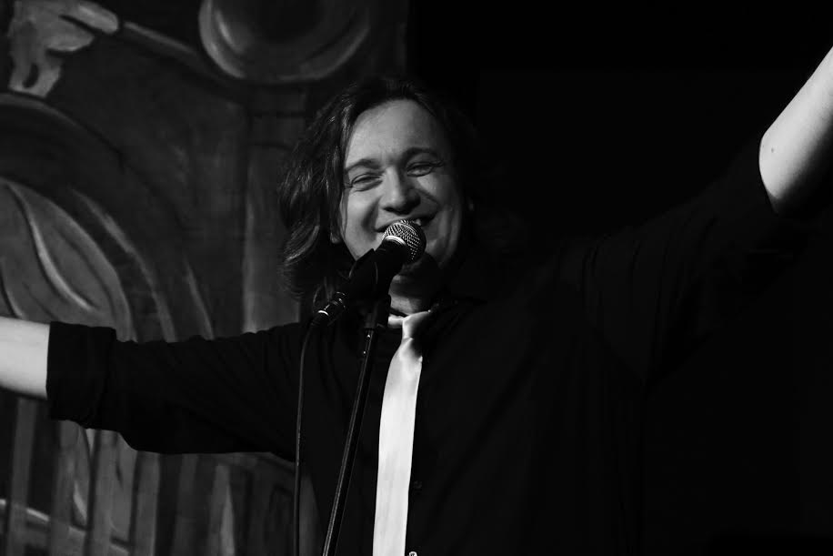 una foto in binco e nero il comico sul palco con le braccia allargate è un ragazzo giovane paffutello con i capelli lunghi scuri